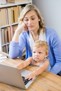 Stressed mother with baby girl using laptop at home